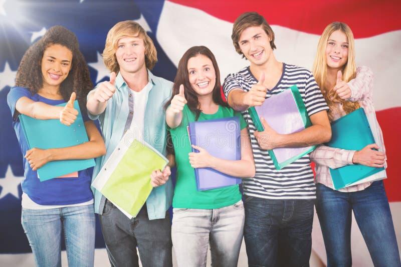 Sammansatt bild av lyckliga högskolestudenter som gör en gest upp tummar royaltyfri fotografi