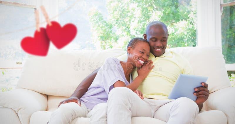 Sammansatt bild av lyckliga le par genom att använda bärbara datorn på soffan arkivfoton