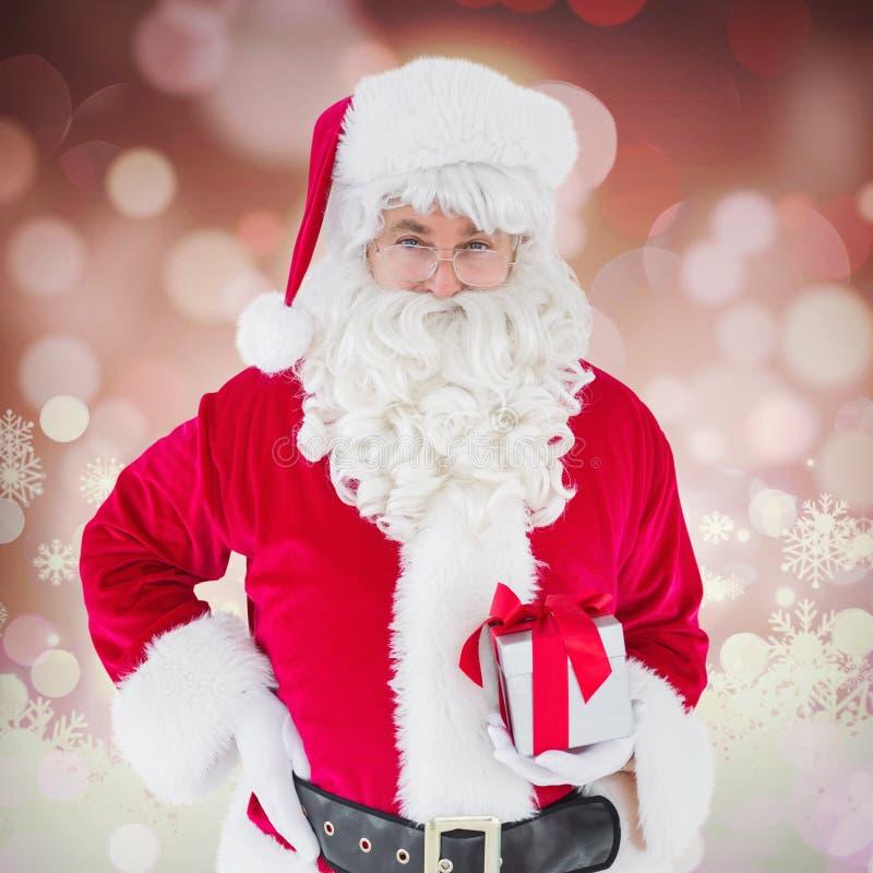 Sammansatt bild av lyckliga Santa Claus som rymmer en gåva royaltyfri fotografi