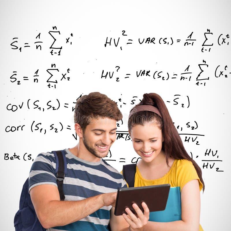 Sammansatt bild av lyckliga studenter som använder minnestavlaPC royaltyfri fotografi