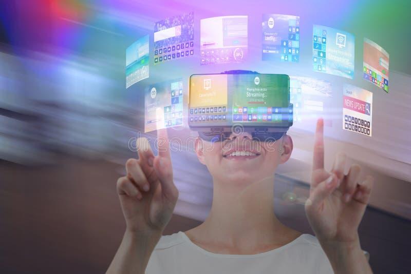 Sammansatt bild av lyckligt peka för kvinna som är uppåtriktat, medan genom att använda virtuell verklighethörlurar med mikrofon arkivbilder