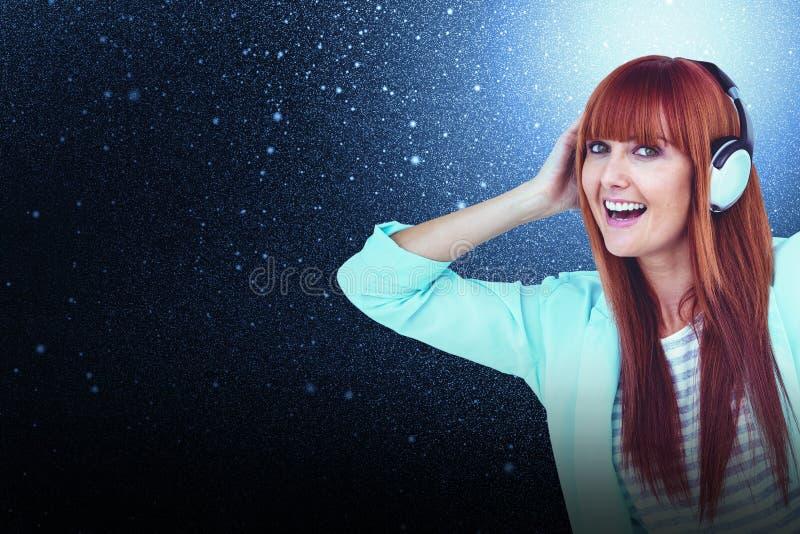 Sammansatt bild av lyssnande musik för lycklig hipsterkvinna med headphonen royaltyfri bild