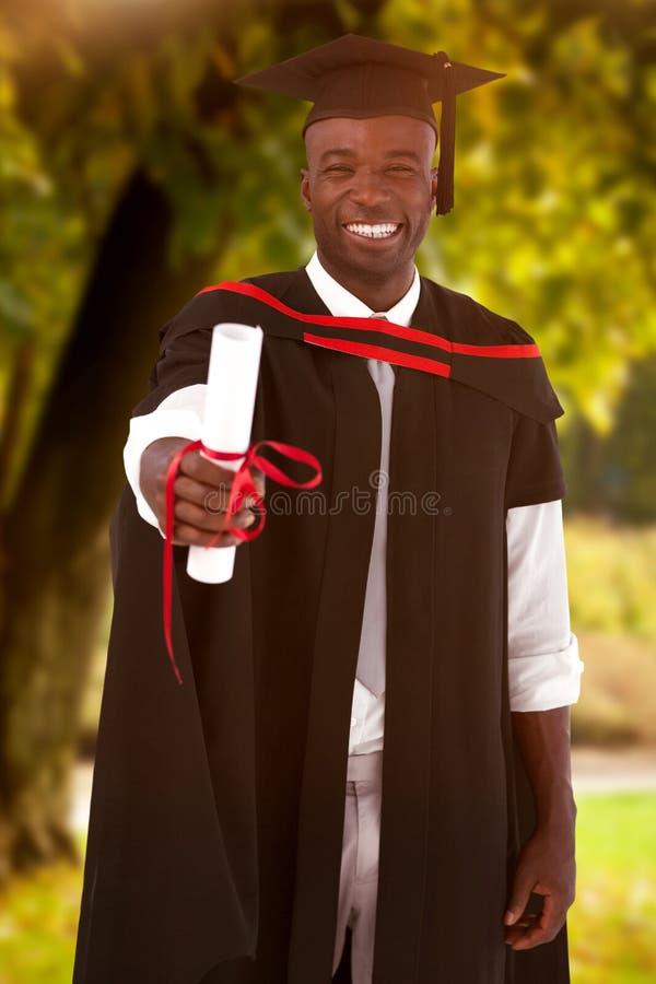 Sammansatt bild av mannen som smilling på avläggandet av examen royaltyfria bilder