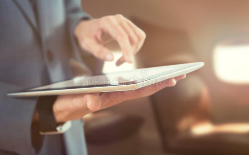 Sammansatt bild av midsectionen av affärsmannen som använder trådlös teknologi arkivfoto