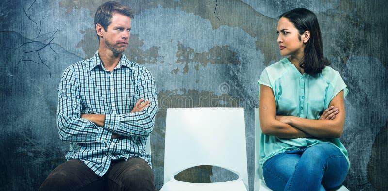 Sammansatt bild av missnöjda par som ser de, medan sitta på stolar arkivfoton