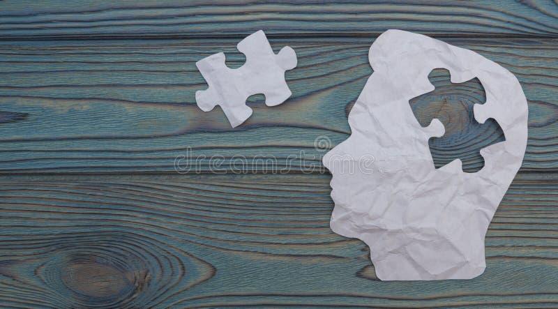 Sammansatt bild av papper i form av ett huvud på en träbakgrund royaltyfri bild