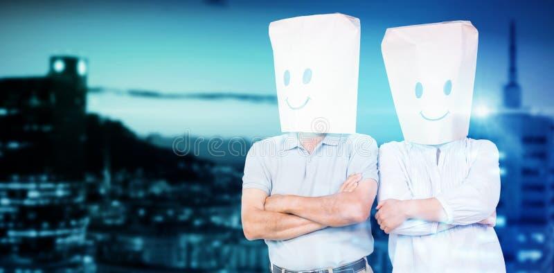 Sammansatt bild av par som bär pappers- påsar på huvudet royaltyfri fotografi