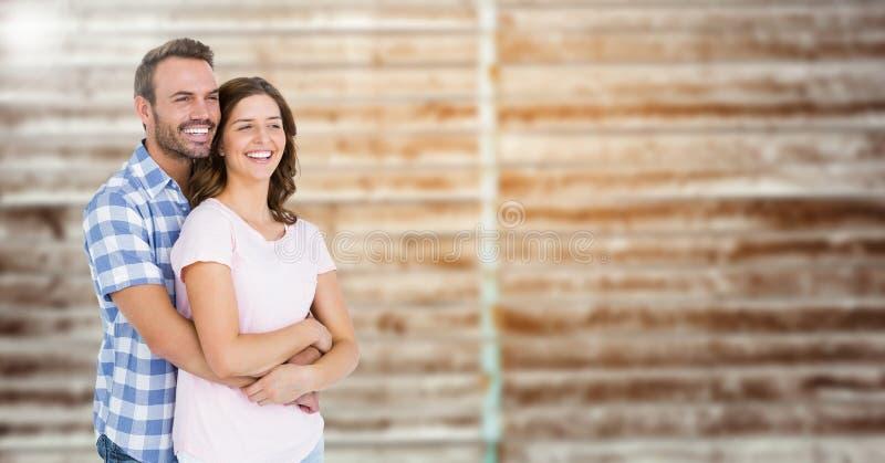 Sammansatt bild av par som omfamnar sig mot tegelstenbakgrund royaltyfria foton