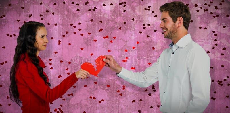 Sammansatt bild av par som rymmer röd sprucken hjärtaform royaltyfria bilder