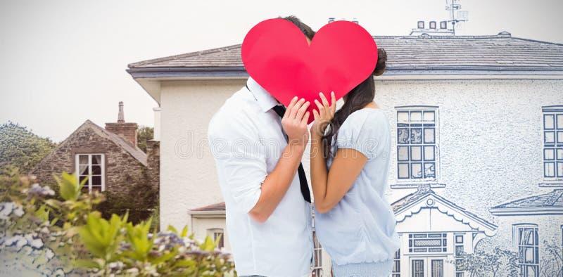 Sammansatt bild av par som täcker deras kyss med en hjärta royaltyfri bild