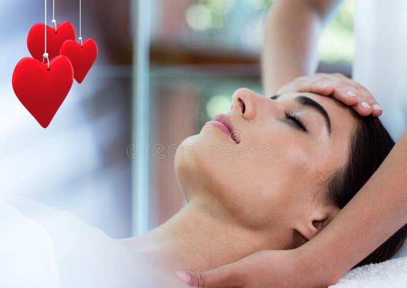 Sammansatt bild av röda hängande hjärtor och kvinnan som mottar en massage arkivfoto