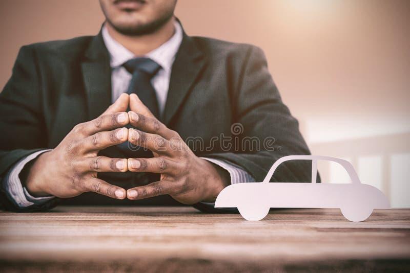 Sammansatt bild av sammanträde för affärsman bak ett skrivbord royaltyfri bild