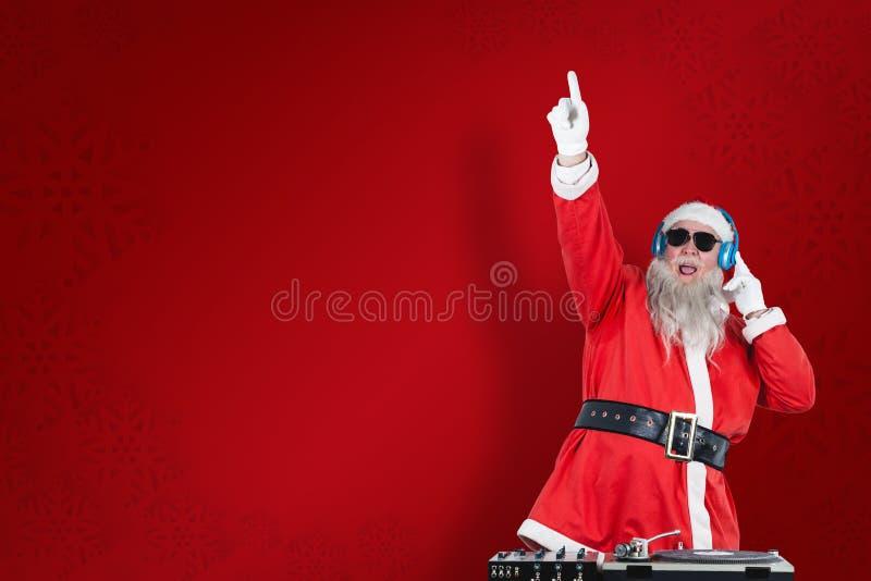 Sammansatt bild av Santa Claus som spelar dj med den lyftta handen arkivfoton