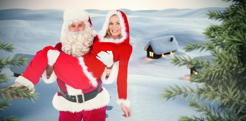 Sammansatt bild av santa och mrs claus som ler på kameran royaltyfria bilder
