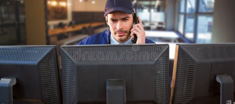 Sammansatt bild av skyddschefen som talar på telefonen, medan genom att använda datoren på skrivbordet arkivfoto