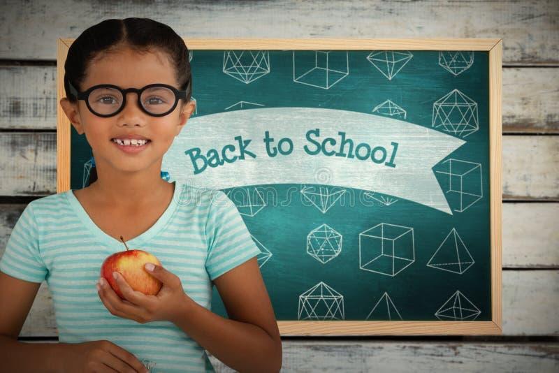 Sammansatt bild av ståenden av att le bärande glasögon för flicka som rymmer äpplet arkivfoto
