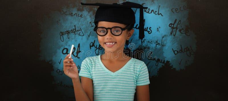 Sammansatt bild av ståenden av att le den bärande akademikermössan för flicka och hållande krita arkivfoto