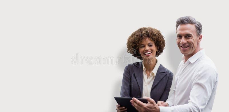 Sammansatt bild av ståenden av affärsfolk som poserar med den digitala minnestavlan royaltyfri foto