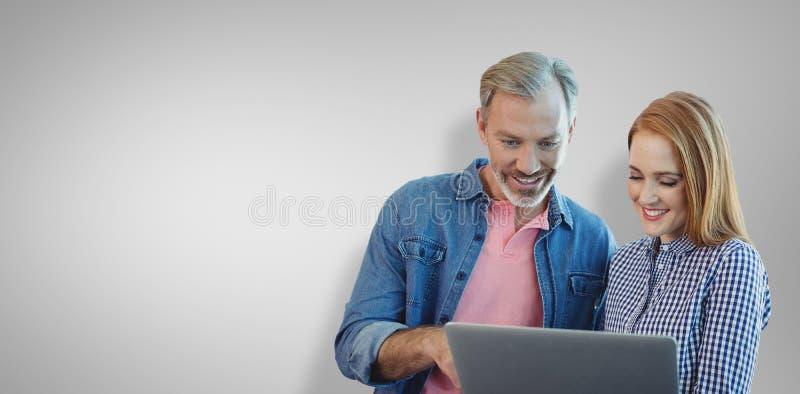 Sammansatt bild av ståenden av att le affärsfolk som använder bärbara datorn royaltyfri bild