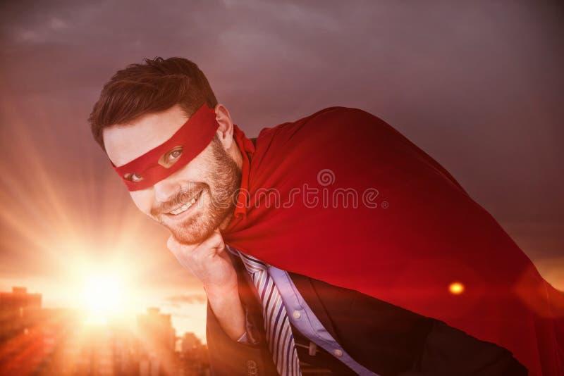 Sammansatt bild av ståenden av att le affärsmannen som låtsar för att vara toppen hjälte royaltyfri bild