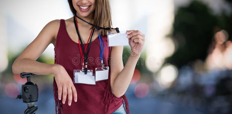 Sammansatt bild av ståenden av det hållande identitetskortet för lycklig kvinna arkivfoton