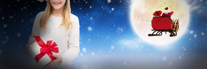 Sammansatt bild av ståenden av den hållande julgåvan för lycklig flicka mot vit bakgrund arkivbild