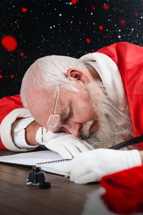 Sammansatt bild av trötta Santa Claus som ta sig en tupplur på skrivbordet, medan skriva ett brev med en vingpenna royaltyfri fotografi