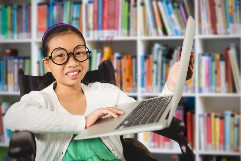 Sammansatt bild av ung flickavisningbärbara datorn, medan sitta på rullstolen royaltyfri bild