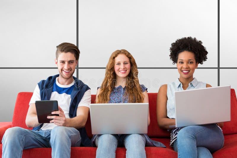 Sammansatt bild av unga vuxna människor som använder elektroniska apparater på soffan arkivbild
