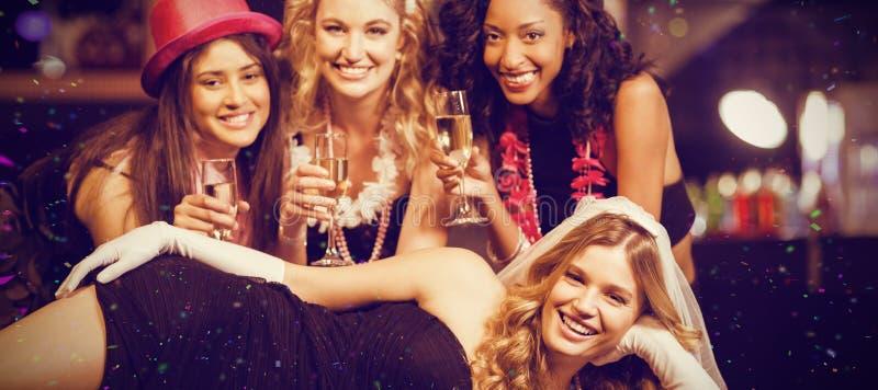 Sammansatt bild av vänner som firar ungmöpartiet royaltyfri fotografi