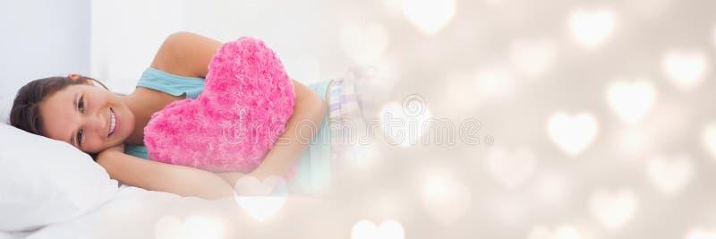 Sammansatt bild med att le flickan i hållande hjärtakudde för säng med hjärtor fotografering för bildbyråer