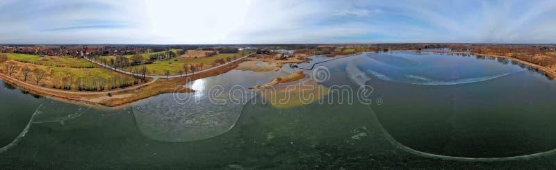 Sammansatt panorama av flyg- fotografier och flygbilder av ett vått villebråd för grus och sand med en nästan fryst sjö och larg arkivfoto