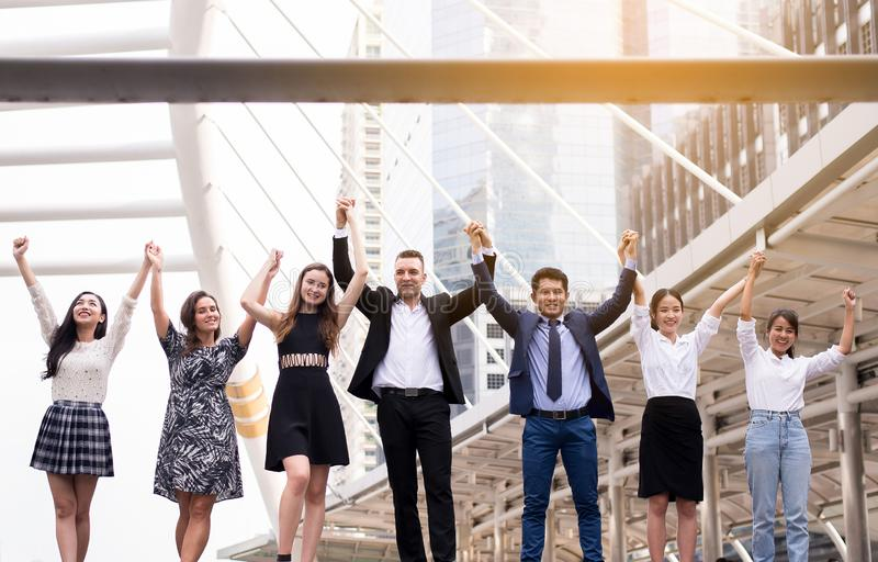Sammanslagningar och förvärv, lyckad grupp av affärsfolk, hand för lagframgångprestation lyftte upp royaltyfri bild