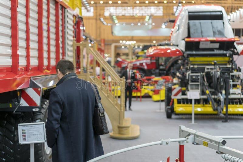 Sammanslutningar, traktorer och maskineri under den jordbruks- utställningen Affärsmannen väljer utrustning för att arbeta i fält arkivbild