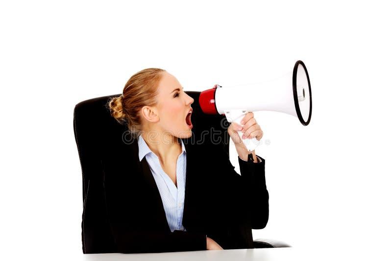 Sammanträde för affärskvinna bak skrivbordet och skrika till och med en megafon arkivbild