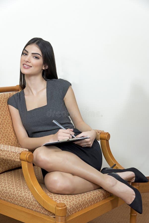 Sammanträde för affärskvinna på en armstol arkivfoton