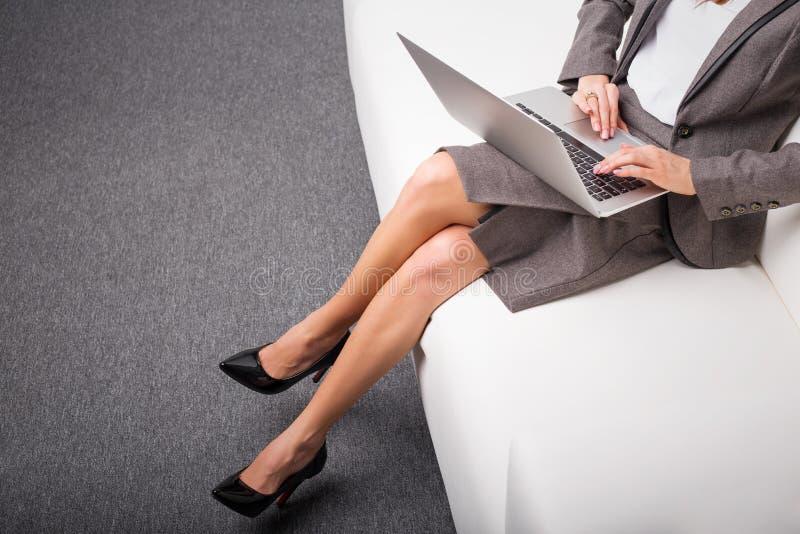 Sammanträde för affärskvinna på soffan med datoren i hennes varv fotografering för bildbyråer