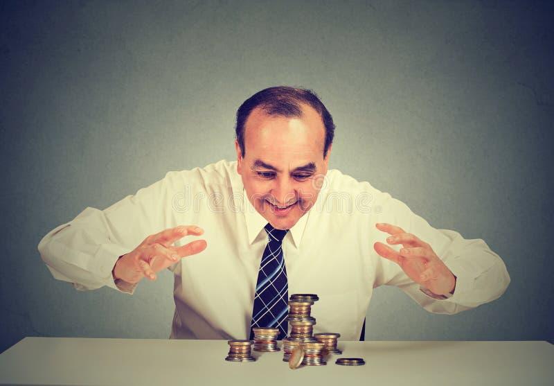 Sammanträde för affärsman på tabellen som ser hans pengar som skyddar dem med händer arkivbild