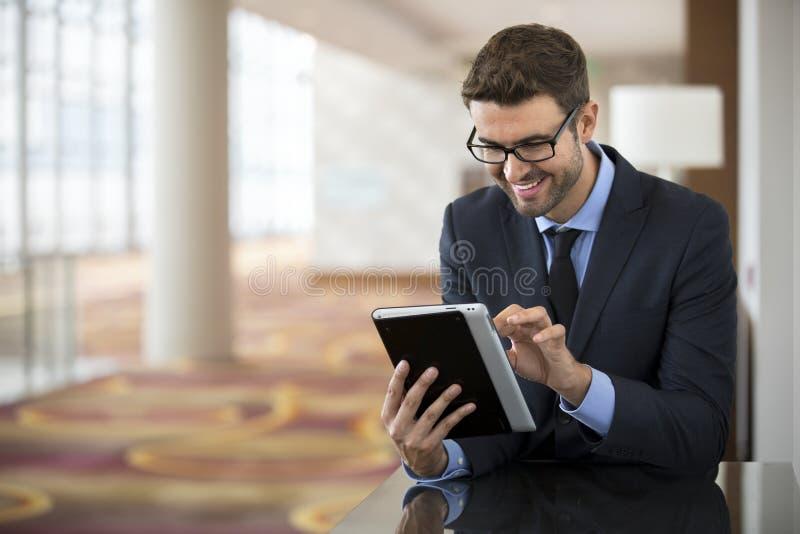 Sammanträde för affärsman som läser en minnestavlaapparat arkivfoto