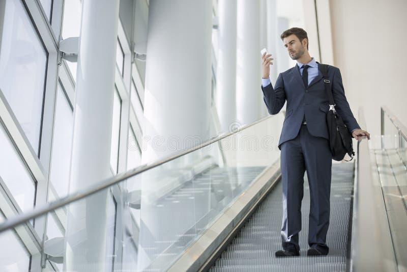 Sammanträde för affärsman som talar på mobiltelefonen medan på rulltrappan arkivfoto