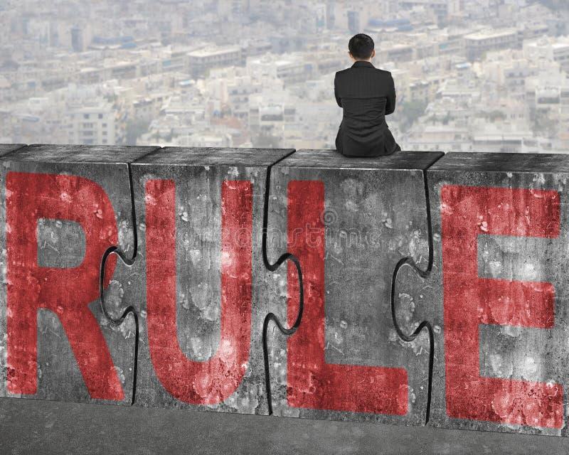 Sammanträde för affärsmannen på betong förbryllar med rött regelord fotografering för bildbyråer