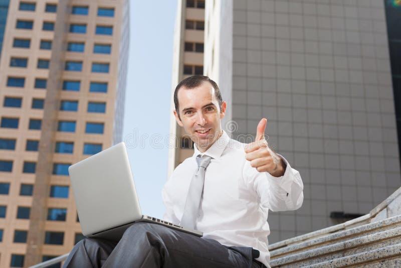 Sammanträde för affärsmannen på moment som använder bärbara datorn, tummar upp arkivbild