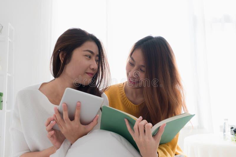 Sammanträde för Asien lesbiskt lgbtpar på sängläseboken och bruksflik royaltyfri foto