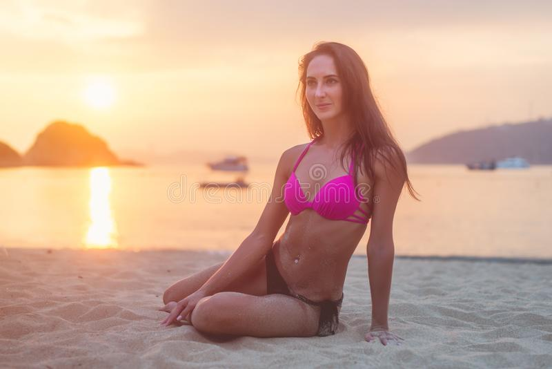 Sammanträde för bikini för attraktiv ung brunettkvinna för passform bärande på havsstranden på solnedgången arkivfoto