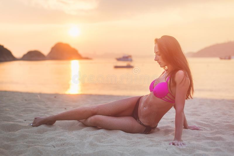 Sammanträde för bikini för attraktiv ung brunettkvinna för passform bärande på havsstranden på solnedgången fotografering för bildbyråer