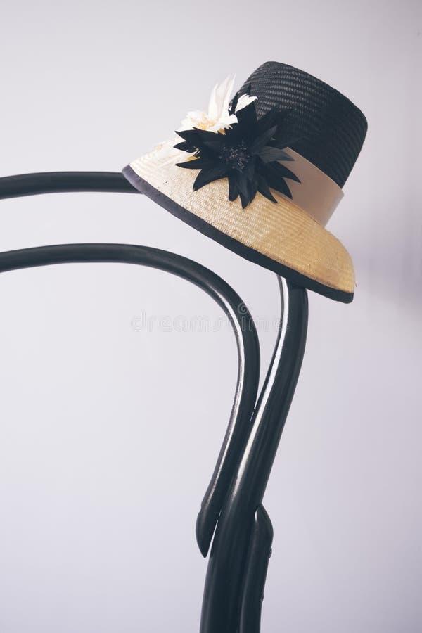 Sammanträde för damklänninghatt på tappningsvarten trästol royaltyfri fotografi