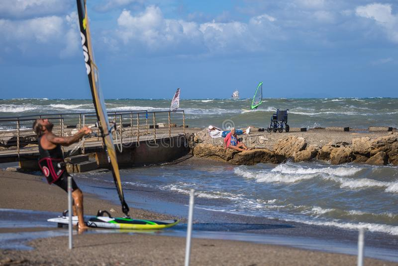 Sammanträde för den gamla kvinnan på vaggar nära kustlinjeblickar på den unga surfaren på stranden arkivfoto
