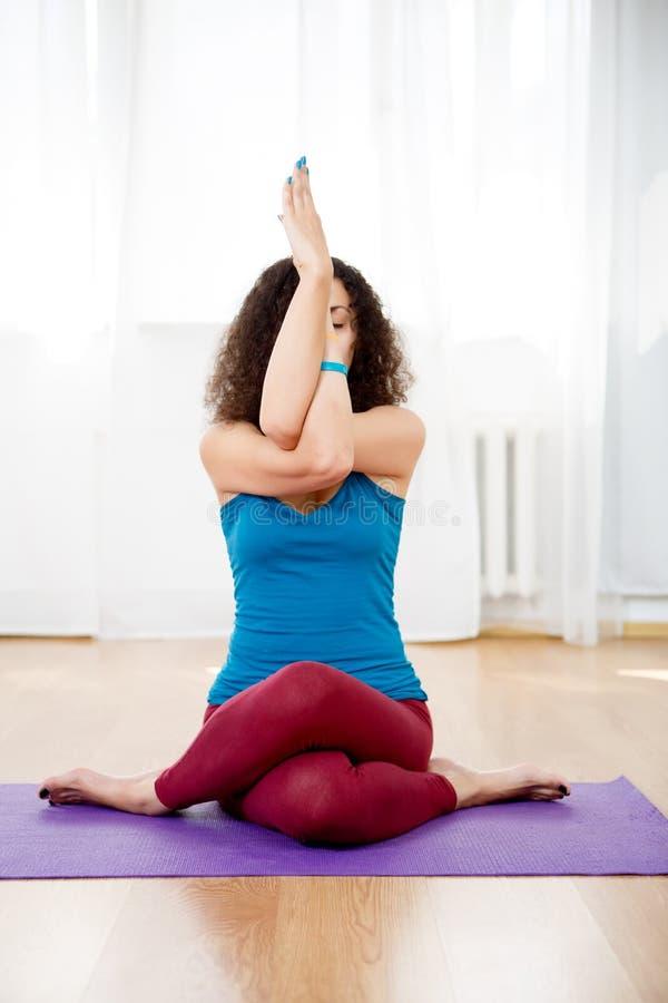 Sammanträde för den unga kvinnan i yoga poserar blandninggomukhasana och garudasana royaltyfria foton