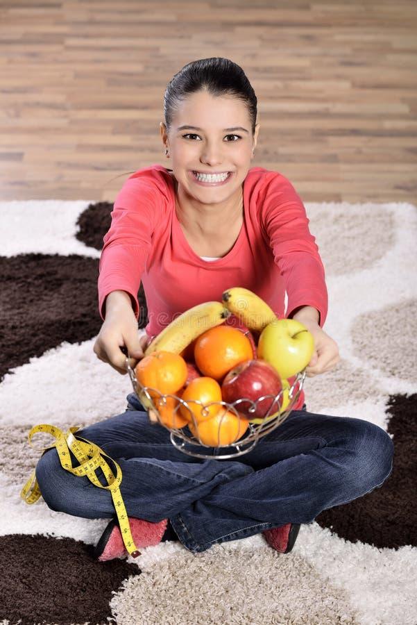 Download Sammanträde För Den Unga Kvinnan På Matta Och Att Tycka Om Bär Frukt Arkivfoto - Bild av lycka, högt: 37346982