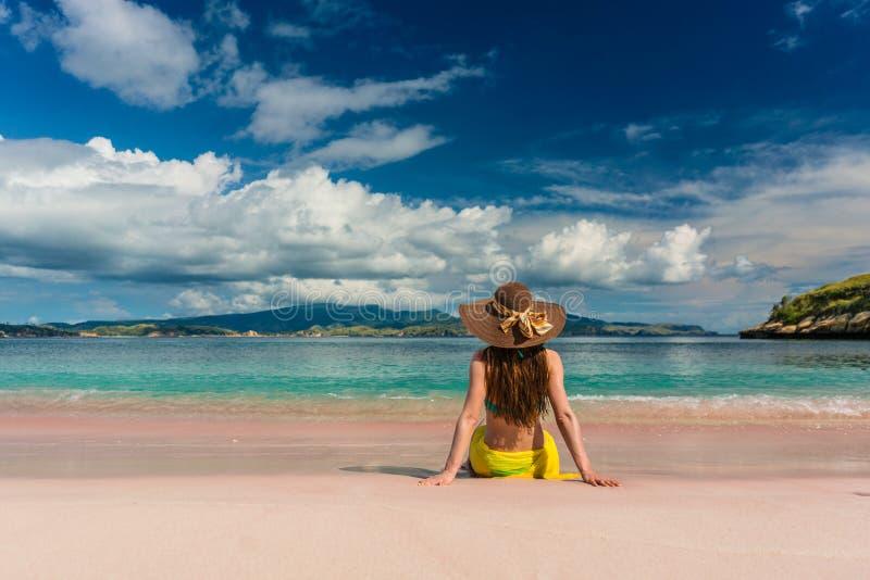 Sammanträde för den unga kvinnan på sanden på rosa färger sätter på land i den Komodo ön arkivfoton
